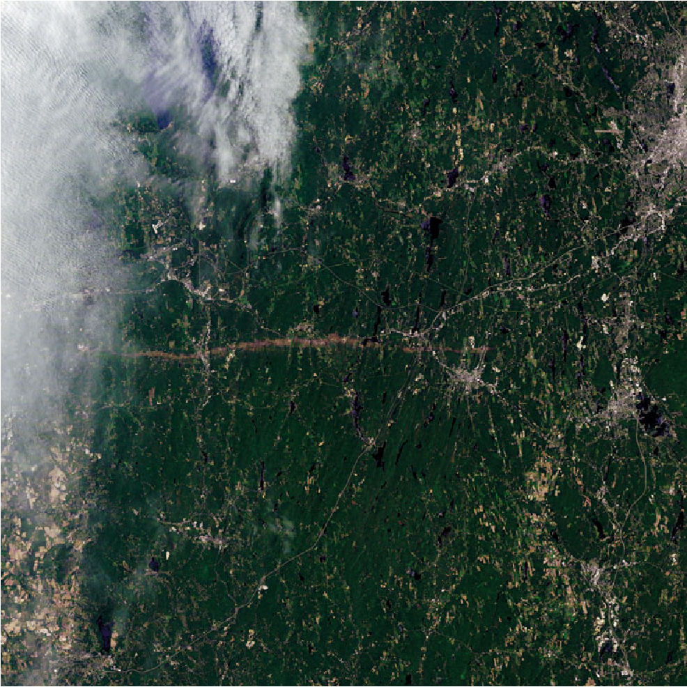 Figure 6.7. Tornado damage track (horizontal brown swath surrounded by greenery from vegetation) over Massachusetts from a tornado on June 1, 2011, as seen by the Landsat 5 satellite.